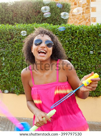 Portrait of african american black teenager girl having fun on a sunny summer day blowing bubbles in suburban street, holiday lifestyle outdoors. Adolescent young woman active living, home exterior. - stock photo