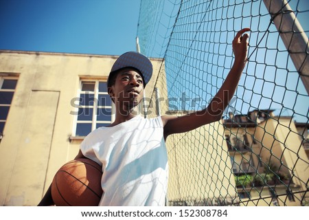 Portrait of african american boy with basketball looking away - stock photo
