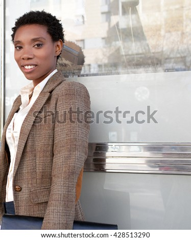 Portrait of african american business woman leaning on reflective glass office building smiling and looking outdoors, financial city exterior. Professional black woman with slick space, exterior. - stock photo