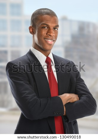 Portrait of African American businessman with arms crossed with office buildings in background - stock photo