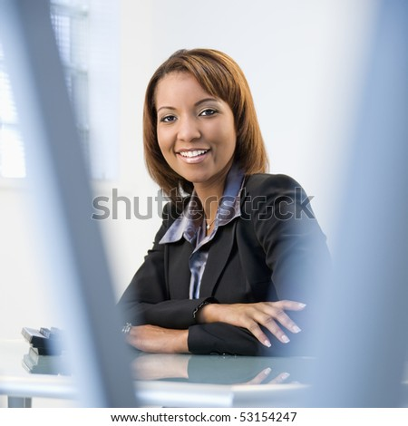 Portrait of African American businesswoman sitting at office desk smiling.