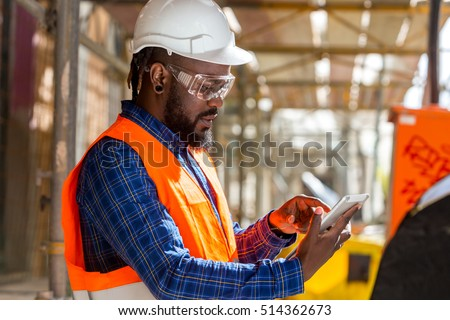 Portrait of African american engineer checking documents on tablet computer
