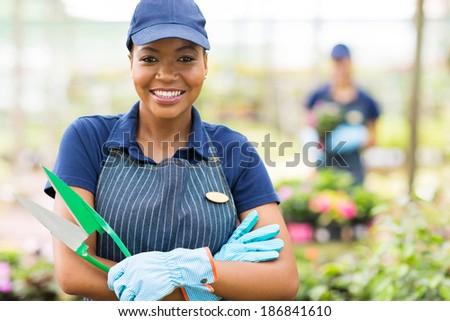 portrait of african american female nursery worker holding a scissors - stock photo