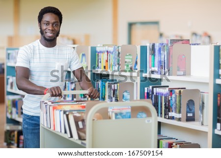Portrait of African American librarian with trolley of books in bookstore - stock photo