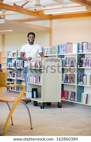 Portrait of African American librarian with trolley of books smiling in bookstore - stock photo