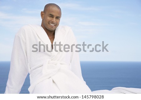 Portrait of African American man in bathrobe with ocean in background - stock photo