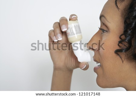Portrait of African American woman using asthma inhaler