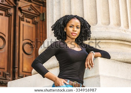 Portrait of African American Woman. Wearing long sleeves, V neck top, a young black college student with braid hairstyle standing by column in vintage style office building on campus in New York.