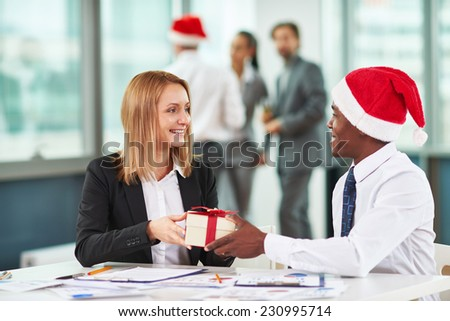 Portrait of African businessman giving Christmas present to Caucasian female colleague - stock photo