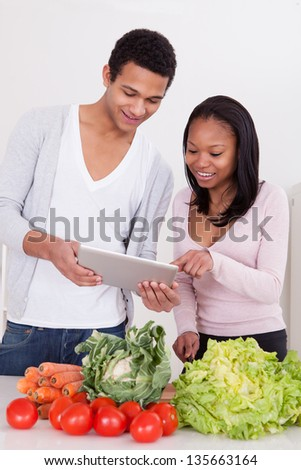 Portrait Of African Couple With Vegetables And Digital Tablet In Kitchen - stock photo