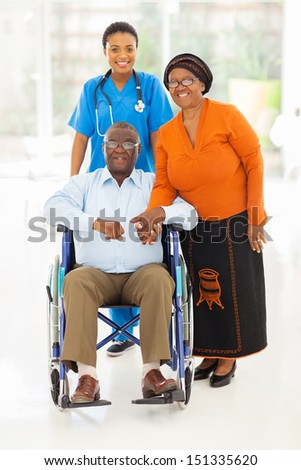 portrait of african female healthcare worker with senior couple at home - stock photo