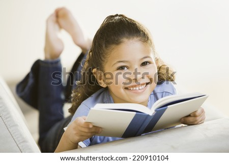Portrait of African girl holding book on sofa - stock photo