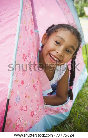 Portrait of African girl leaning out of tent - stock photo