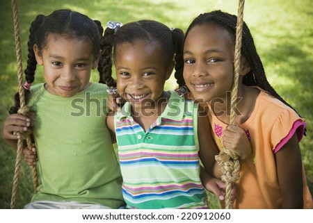 Portrait of African girls on swing - stock photo
