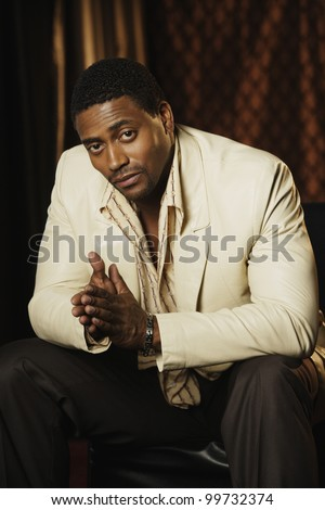 Portrait of African man rubbing hands together - stock photo