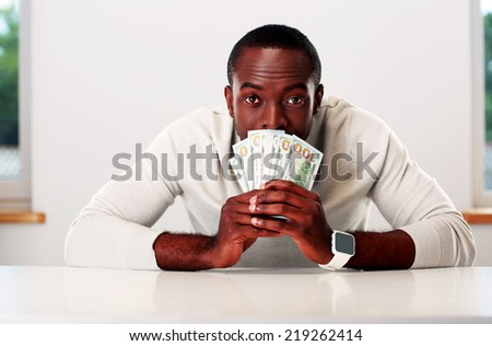 Portrait of african man sitting at the table and holding US dollars - stock photo