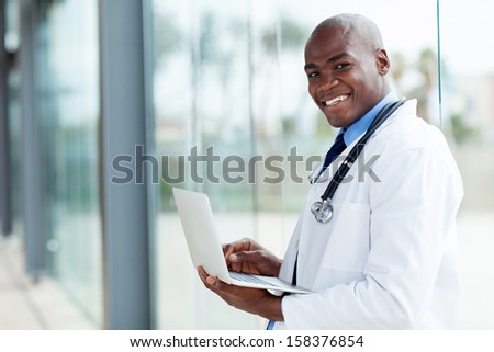 portrait of afro american doctor using laptop computer - stock photo