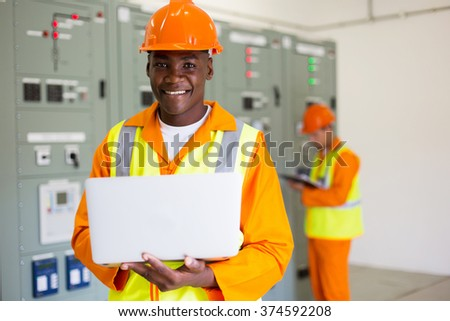 portrait of afro american engineer using laptop computer in control room - stock photo