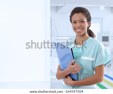 Portrait of afro-american female nurse at hospital corridor, smiling. Large copyspace on left. - stock photo
