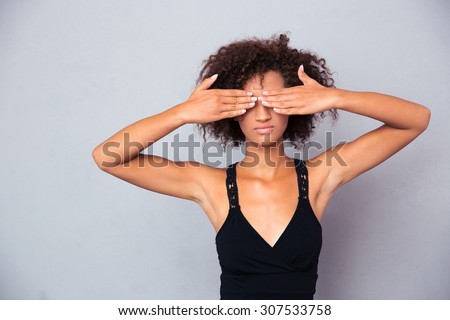 Portrait of afro american woman covering her eyes over gray background - stock photo