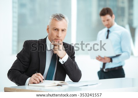 Portrait of aged and young businessmen in office with big window. Businessmen having meeting