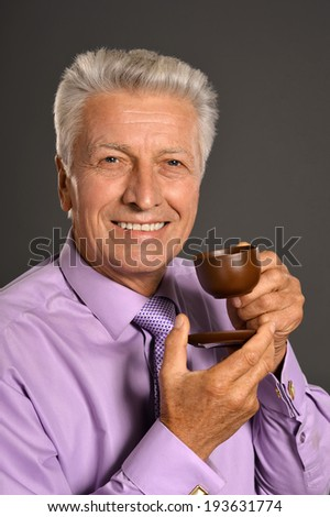 Portrait of aged businessman drinking coffee on a gray background