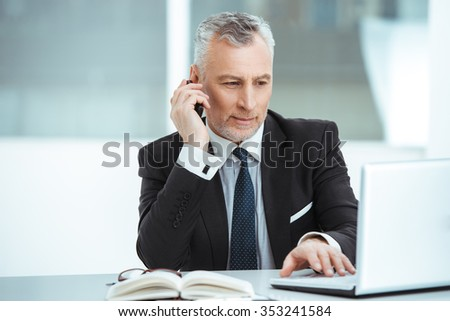 Portrait of aged businessman wearing suit and tie. Businessman in years is in office with big window. Boss using mobile phone