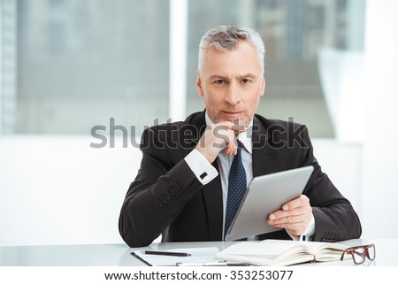 Portrait of aged businessman wearing suit and tie. Businessman in years is in office with big window. Boss using tablet computer