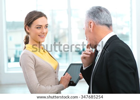 Portrait of aged businessman with his assistant. Businessman in years standing in office with big window. Boss looking at tablet computer