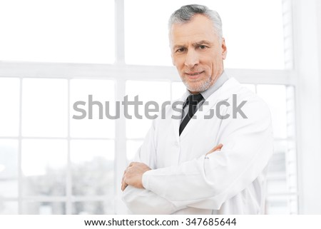 Portrait of aged doctor wearing lab coat. Doctor in years standing in hospital office with big window. Medico smiling and looking at camera - stock photo