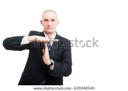 Portrait of aged elegant man showing time out gesture wearing suit and tie isolated on white background  with copy text space