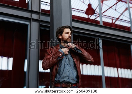 Portrait of aged fashionable hipster man with beard buttoning a shirt standing against glassy reflective wall indoors - stock photo