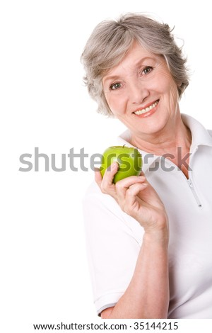 Portrait of aged female holding an apple and smiling - stock photo