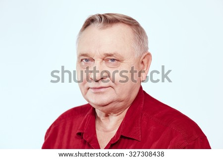 Portrait of aged man wearing red shirt against white background - retirement concept