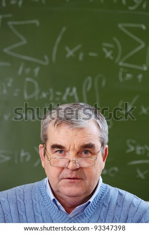 Portrait of aged teacher looking at camera with blackboard on background - stock photo