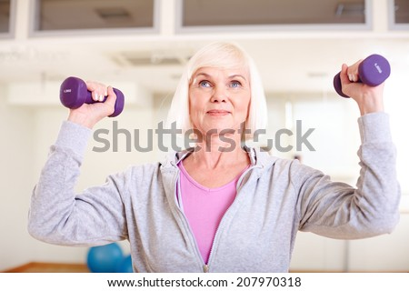 Portrait of aged woman doing exercise with barbells - stock photo