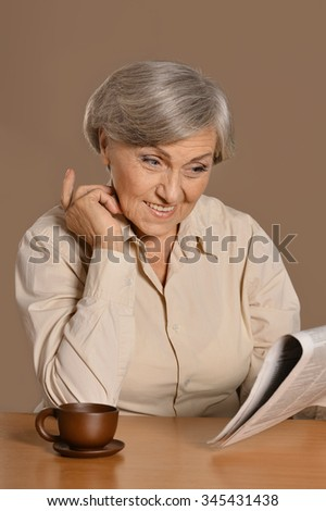 Portrait of aged woman drinking coffee on brown background - stock photo