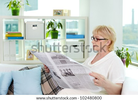 Portrait of aged woman reading newspaper at home - stock photo