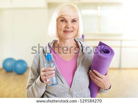 Portrait of aged woman with bottle of water and rug looking at camera - stock photo