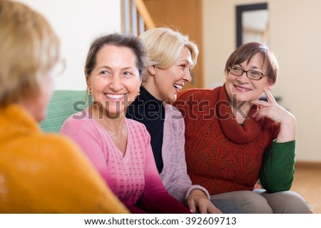Portrait of aged women having discussion indoor and smiling. Focus on blonde