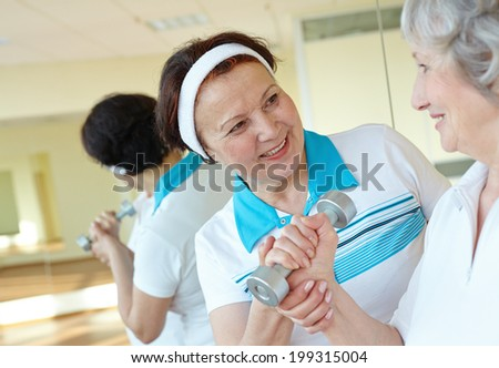 Portrait of aged women interacting in sport gym - stock photo