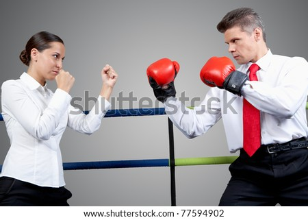 Portrait of aggressive businessman in boxing gloves and serious female in conflict with each other - stock photo