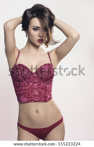 portrait of alluring girl with brown hair and cute make-up wearing red sexy underwear in sensual pose  - stock photo