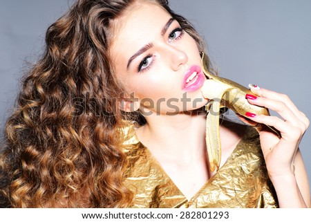 Portrait of alluring young girl with curly hair in gold jacket holding and eating golden banana looking forward standing on grey background, horizontal picture