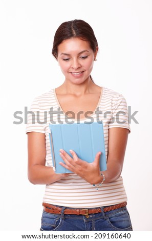 Portrait of alone beautiful lady on brown t-shirt and blue jeans looking at her tablet pc while standing on isolated studio