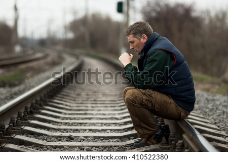 portrait of alone man on railway - stock photo