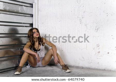 Portrait of alone young urban girl sitting in a corner - stock photo