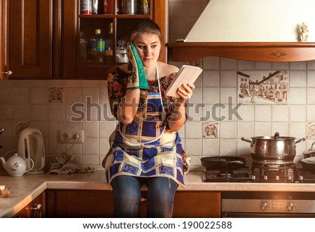 Portrait of amazed housewife looking recipe on tablet while sitting on tabletop - stock photo