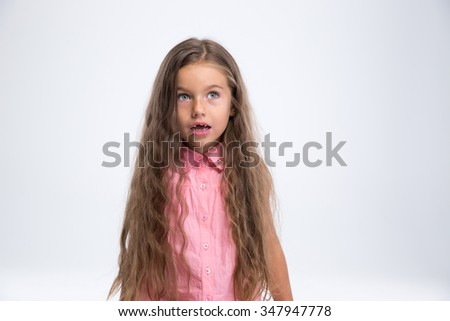 Portrait of amazed little girl looking away at copyspace isolated on a white background  - stock photo