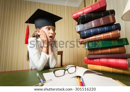Portrait of amazed smart girl in graduation cap looking at big heap of books - stock photo